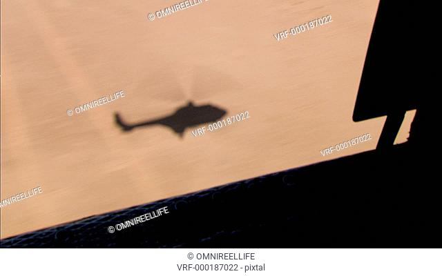 View from open door of helicopter of helicopter shadow on desert below