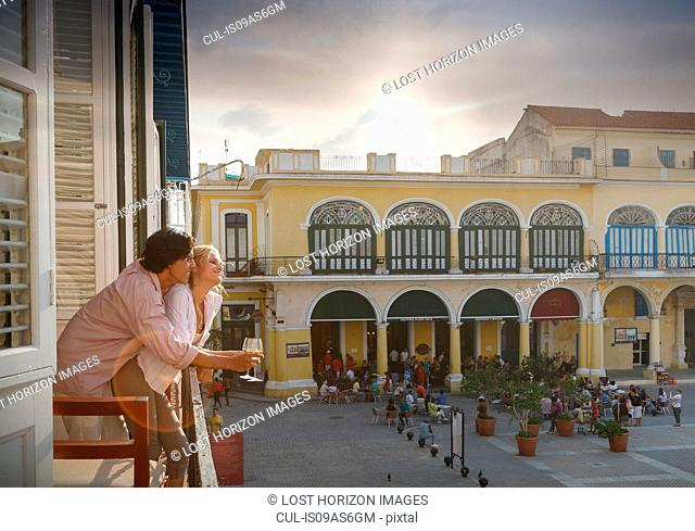 Romantic young couple looking out from restaurant balcony in Plaza Vieja, Havana, Cuba