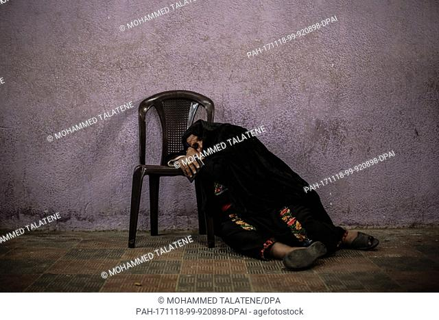dpatop - An elderly Palestinian woman takes a rest as she awaits clearance to take a bus to travel through the Rafah border crossing with Egypt at a makeshift...
