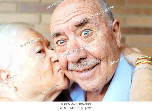 Senior man pulling funny face while his wife kissing him