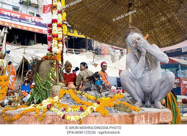 Hindu saint naga baba Shivdasgiri smoking tobacco in Varanasi on Ganga river ; Uttar Pradesh ; India MR707A