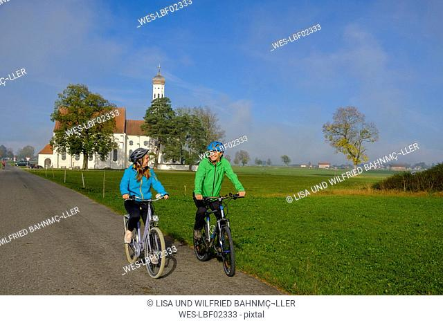 Germany, Pilgrimage Church St. Coloman and couple of cyclists on tour