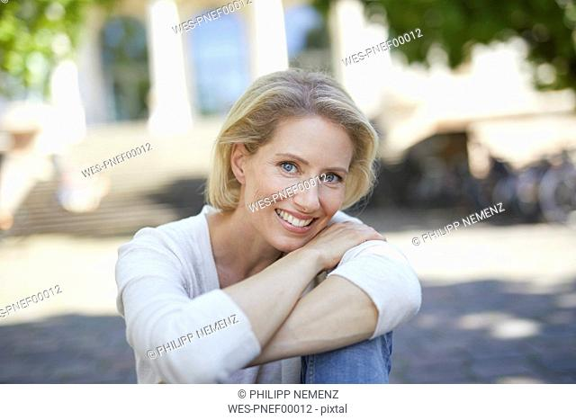 Portrait of smiling blond woman with arms crossed