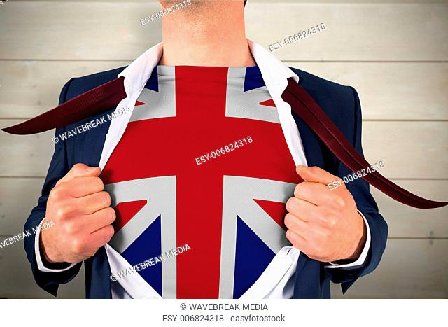 Composite image of businessman opening shirt to reveal union jack flag