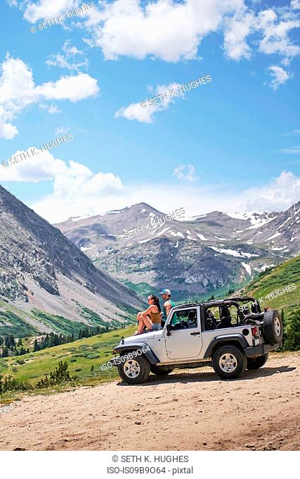 Road trip couple looking out at mountains from off road vehicle hood, Breckenridge, Colorado, USA