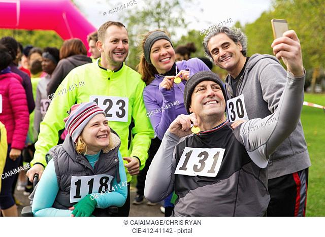 Friends with medals taking selfie at charity race in park