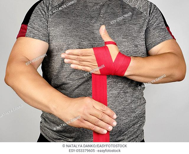 athlete stand in gray clothes and wrap his hands in red textile elastic bandage before training, gray background