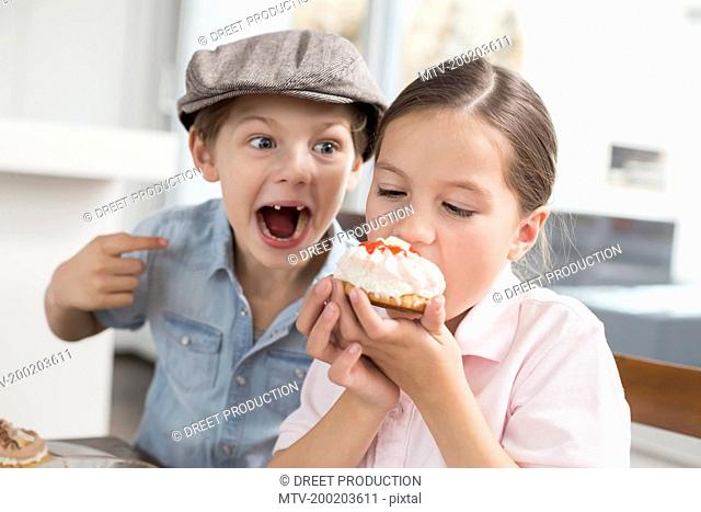 Playful brother and sister eating cake
