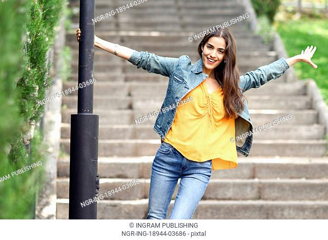 Young woman with nice hair wearing casual clothes in urban background. Happy girl with wavy hairstyle