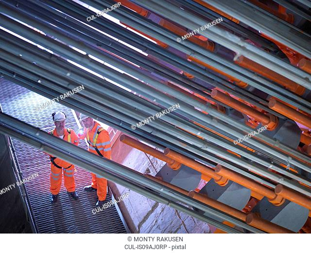 Civil engineers using torch to inspect cable anchorage in suspension bridge. The Humber Bridge, UK, built in 1981 was the world's largest single-span suspension...