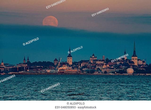 Full moon over Old town of Tallinn city, Estonia. Moonset before sunrise