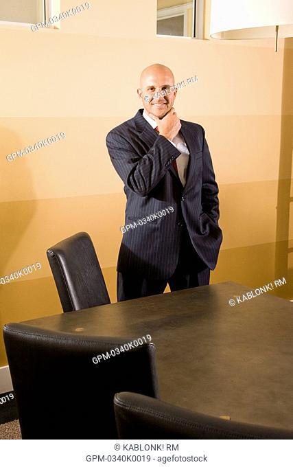 Mid adult businessman standing in boardroom