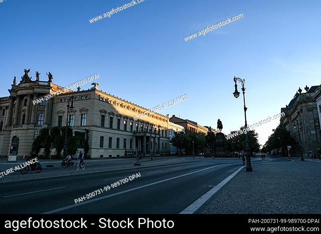 23 July 2020, Berlin: The building of the Old Library and other houses Unter dem Linden at the equestrian monument of Friedrich II are only illuminated at the...