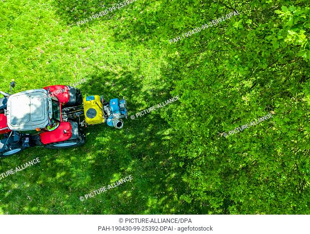 30 April 2019, North Rhine-Westphalia, Heek: On behalf of Straßen.NRW, a tractor of a contracting company sprayed with a biocide on the motorway rest areas...