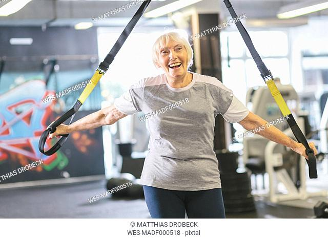 Happy senior woman in gym doing suspension training