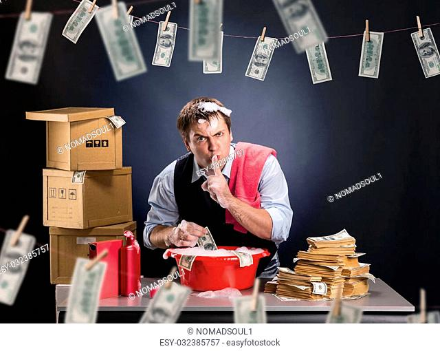 Businessman is laundering money banknotes in foam in red washbowl