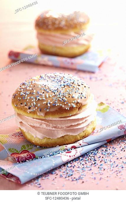 A glazed carnival doughnut filled with raspberry cream