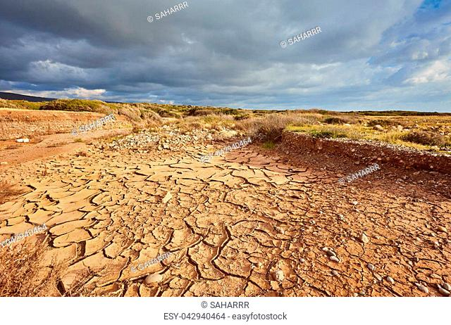 global warming. deep blue sky with clouds over drought earth