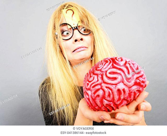 Weird blonde woman holding brain having something on mind, thinking of idea