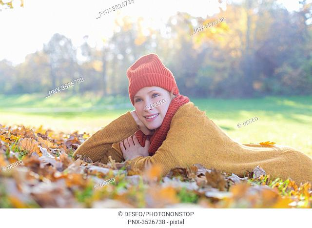Pensive blonde woman lying in park in autumn