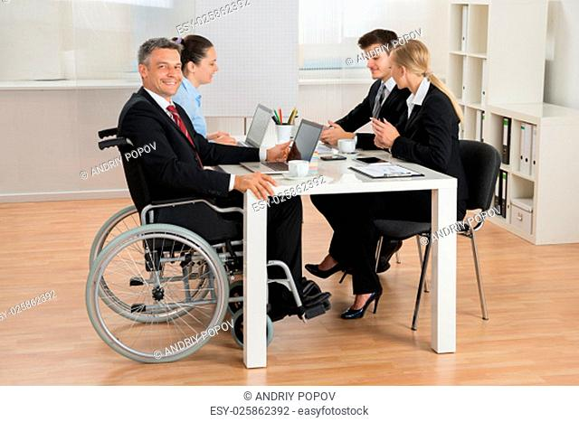 Happy Mature Disabled Businessman Having Meeting With Colleagues In Office