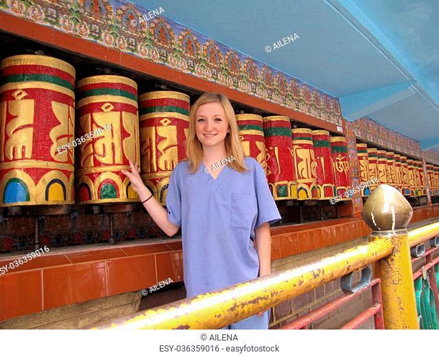 McLeod Ganj India blond tourist volunteer in medical scrubs in front of Tibetan prayer wheels, Tibetan temple