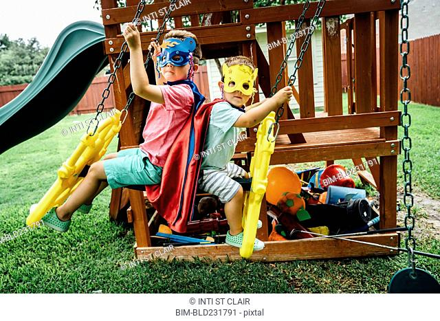 Caucasian brothers wearing superhero costumes on swing
