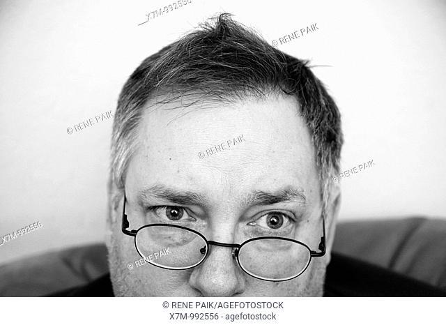 Man quizzically peering over his eyeglasses