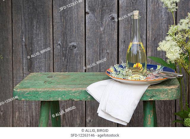 Homemade elderberry blossom oil in a bottle, on a plate