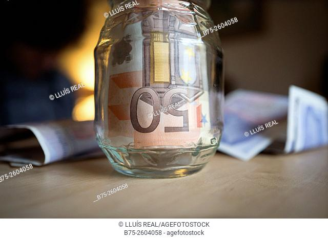 Euro bills in a glass jar