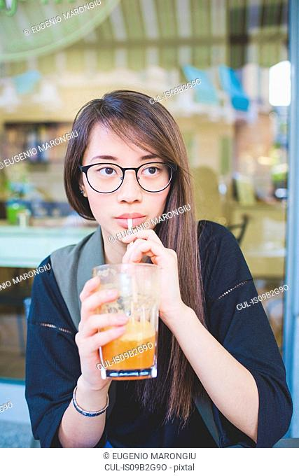 Young woman drinking smoothie at sidewalk cafe