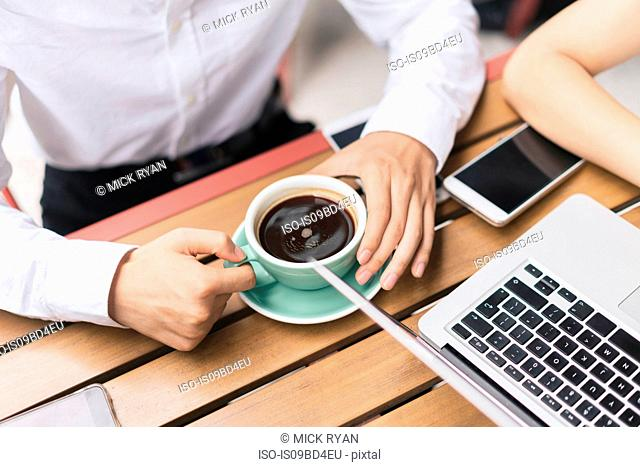 Two businesspeople, having meeting at cafe, using laptop, mid section