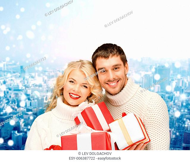 christmas, holidays, happiness and people concept - smiling man and woman with presents over snowy city background