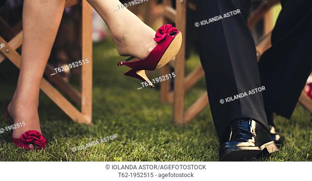 Plan of the legs of two guests at a wedding during the ceremony