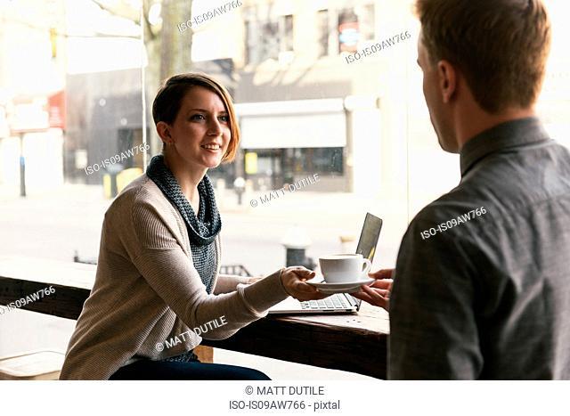 Waiter handing coffee to female customer sitting in coffee shop window