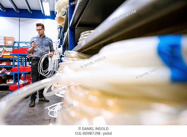 Male manager inspecting cable product in factory warehouse