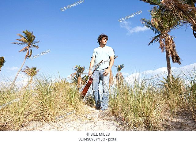 Young man holding guitar on beach
