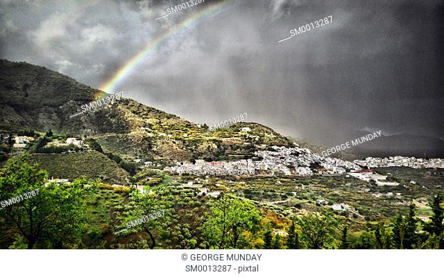 Stormy evening with Rainbow over Frigiliana,. Costa del Sol, Malaga Province,. Andalucia, Spain