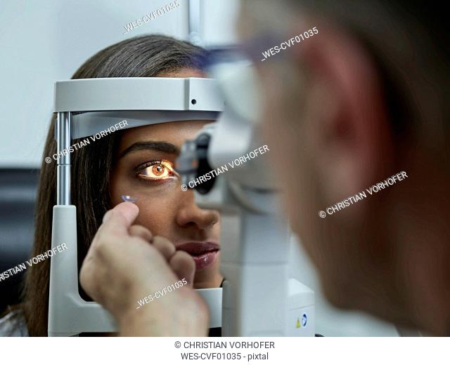 Optometrist examining young woman's eye, contact lens on index finger