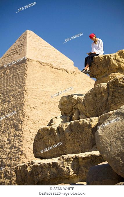 A Female Tourist Reads A Guide Book While Sitting In Front Of The Pyramids Of Giza Near Cairo, Giza Egypt