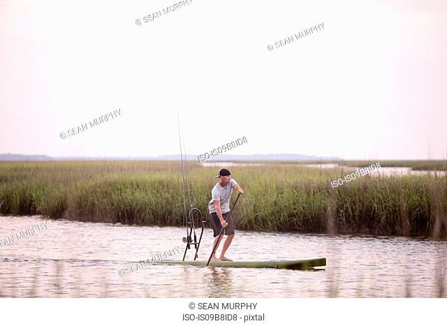 Mature man paddle boarding on water