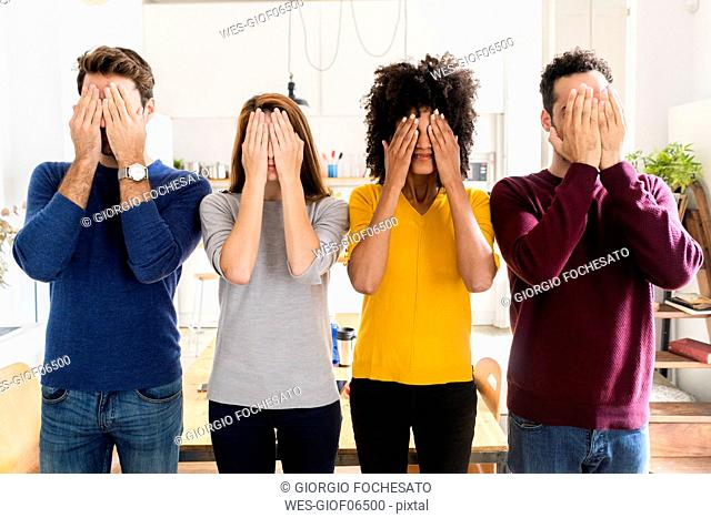 Four friends standing side by side at home covering their faces