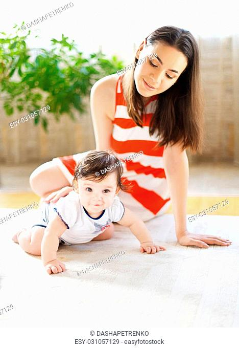 Happy smiling mother with eight month old baby girl indoor