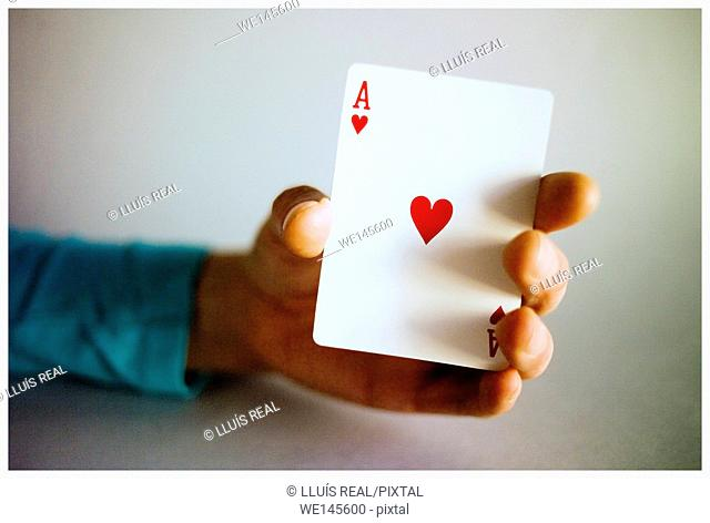 Hand of young woman showing a playing card ace of hearts