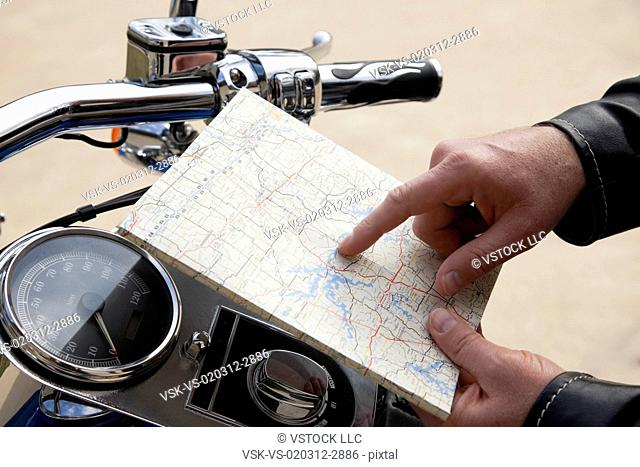 USA, Illinois, Metamora, Close up of man's hand holding map near motorcycle handlebars