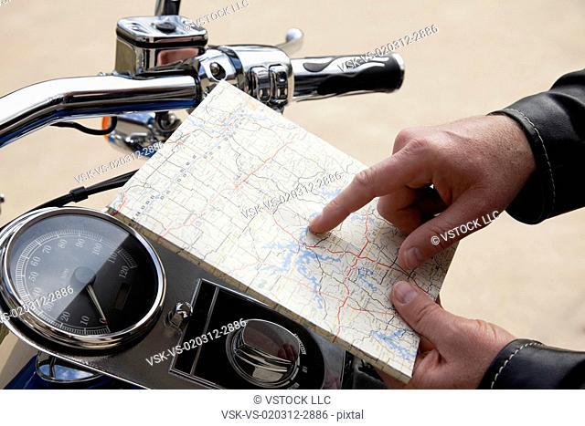 USA, Illinois, Metamora, Close up of man's hand holding map near motorcycle handlebars