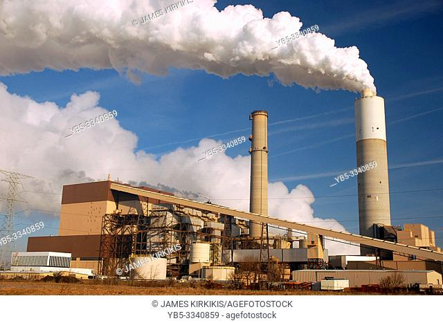 A smoke stack belches smog into a blue sky