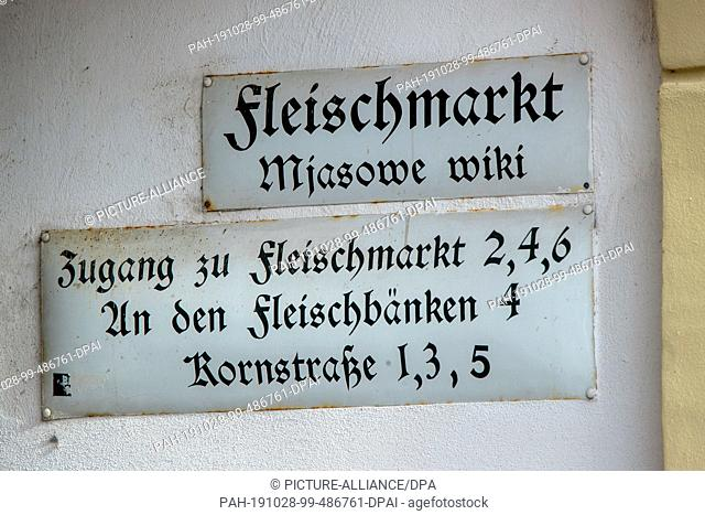 17 October 2019, Saxony, Bautzen: Historical street and information signs hang on the meat market in the old town. Bautzen, Upper Sorbian Budy·in
