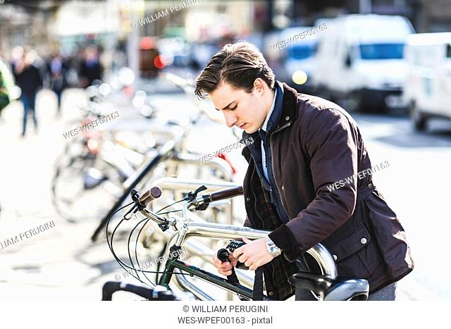 Businessman locking bicycle in the city