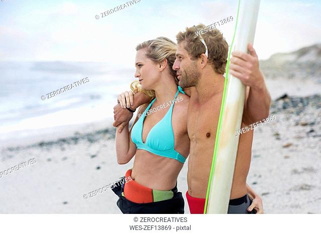 Couple on the beach with surfboard